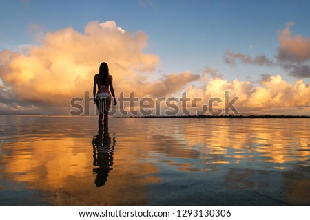 Silhouetted woman standing in a water at sunset on Taveuni Island, Fiji. Taveuni is the third largest island in Fiji.