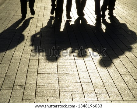 Photo of  Silhouettes and shadows of people on the street. Crowd walking down on sidewalk, concept of strangers, crime, mafia, society, street gang