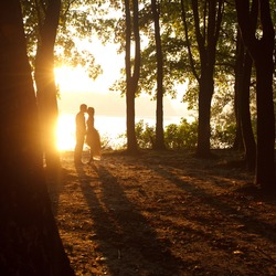 Silhouettes - couple kisses in the light of summer sun