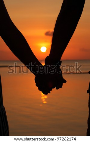 Silhouettes couples hands on sunset