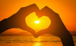 Silhouettes hand heart shaped with sunset and sea background