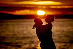 silhouettes in love romantic couple lovers hugging, kissing, touching, eye contact at sunset, sunrise on the background of the sea, the sun, the clouds in fiery red, orange colors