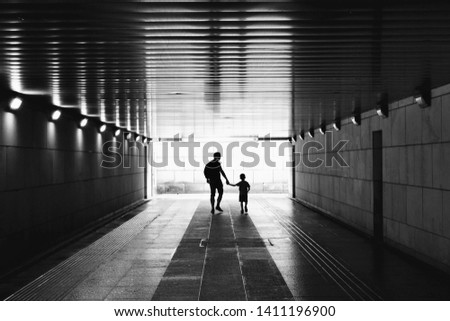 Silhouettes in the tunnel - man and little child walking through empty, dark corridor. Underground passage. Unpleasant, dark place. Kidnapping, stranger, danger, child safety concept. Black and white