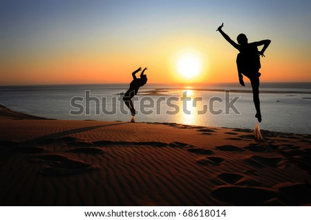 silhouettes jumping on beach in sunset for fun