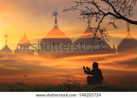 Silhouettes Muslim prayer,the light of faith, hope, faith, supplication,Concept of Islam is the religion, Young Muslim man praying mosque blurred background