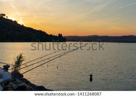 silhouettes of a fishermans fishing rods at Balaton Hungary during sunset #1411268087