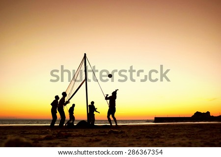 Silhouettes of a group of young people playing beach volleyball during sunset, on the beach in Brittany, France