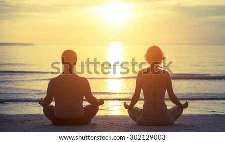 Silhouettes of a young couple sitting in the yoga Lotus position on the banks of the sea during sunset.