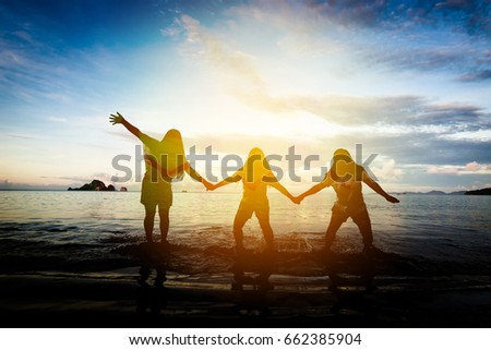 Silhouettes of A young woman group is jumping at on the beach #662385904