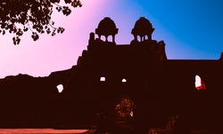 Silhouettes of an Old Fort in Delhi with blue and pink sky background. Famous historical travel destination in India known as Purana Qila or Quila. Abstract background and history concept.