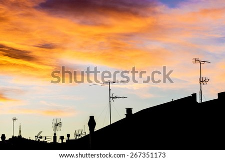 Silhouettes of antennas backlit at sunset with colorful sky clouds