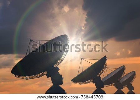 Silhouettes of array of satellite dishes or radio antennas at sunset. - Shutterstock ID 758445709