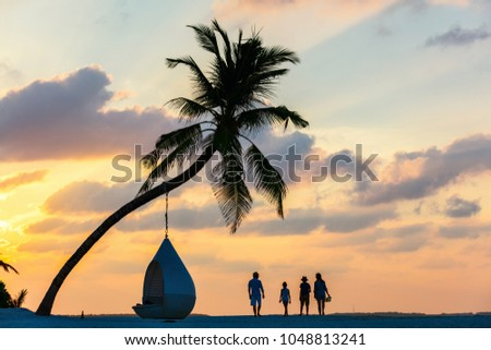 Silhouettes of beautigul family pf four with kids at tropical beach during sunset