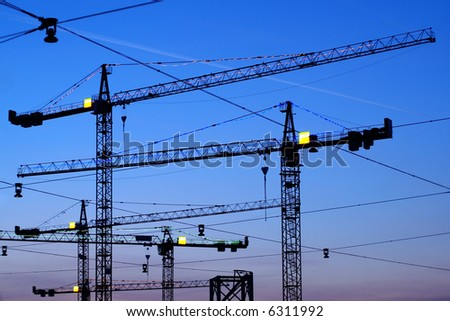 Silhouettes of building cranes on a background of the evening sky