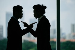 Silhouettes of business partners blaming each other
