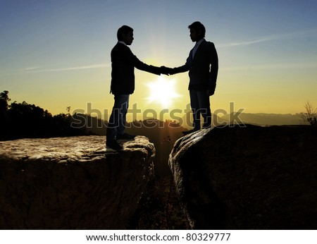 Silhouettes of business partners ,Shake