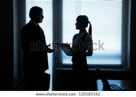 silhouettes of business partners talking against the window in the office