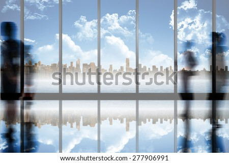 Silhouettes of business people against room with large window looking on city skyline