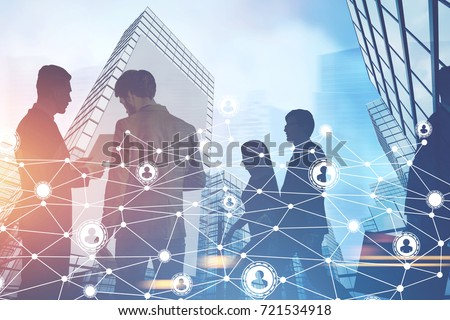 Silhouettes of business people communicating and standing against a cityscape. Bright sky. Network. Toned image double exposure
