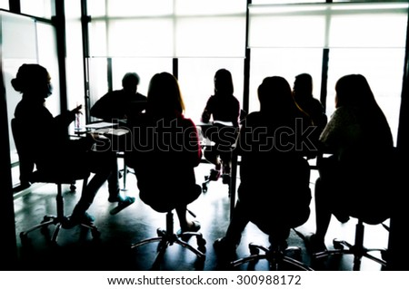Silhouettes of Business People Having Board Meeting. Blur or Defocus image.