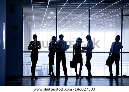 silhouettes of business people rushing for the large windows in the background