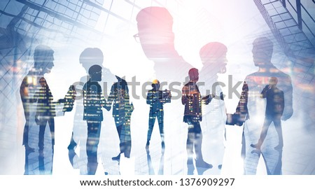 Silhouettes of business people using gadgets, talking and shaking hands over skyscraper background with double exposure of night city panorama. Business lifestyle. Toned image