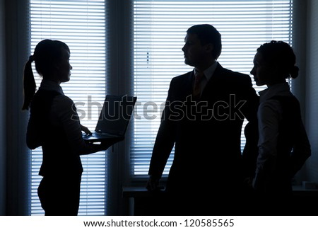 Silhouettes of business team talking on the background of the window in the office