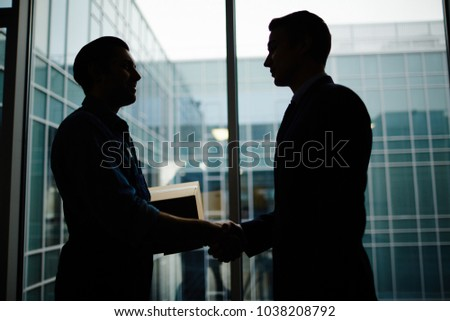 Silhouettes of businessman and delivery man with box shaking hands by office window