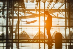 Silhouettes of Businessman and His suitcase Waiting for the plane