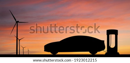 Silhouettes of charging electric car and wind turbines. Getting electricity from renewable energy sources Foto stock ©