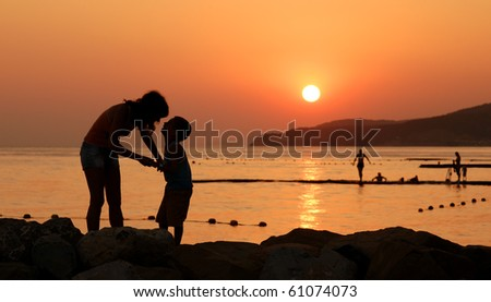 Silhouettes of child and his mother against orange sunset at sea