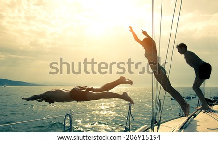 Silhouettes of children diving from the bow of a boat #206915194
