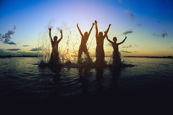 Silhouettes of children jumping in the river