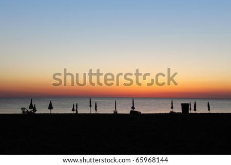 Silhouettes of  closed umbrellas and deck-chairs on  beach during sunset