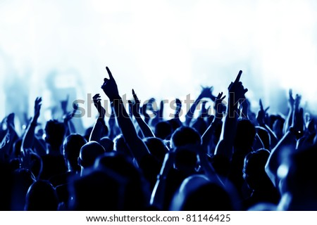 silhouettes of concert crowd in front of bright blue stage lights