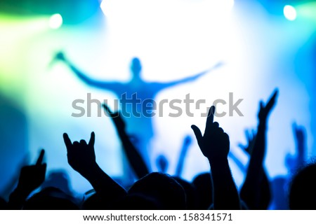 silhouettes of concert crowd in front of bright stage lights #158341571
