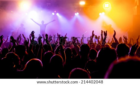 silhouettes of concert crowd in front of bright stage lights #214402048