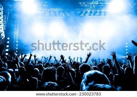 silhouettes of concert crowd in front of bright stage lights #230023783
