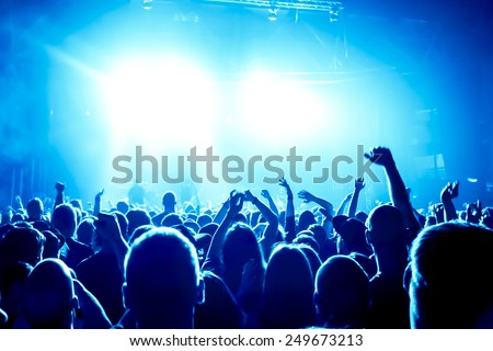silhouettes of concert crowd in front of bright stage lights #249673213