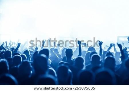 silhouettes of concert crowd in front of bright stage lights #263095835