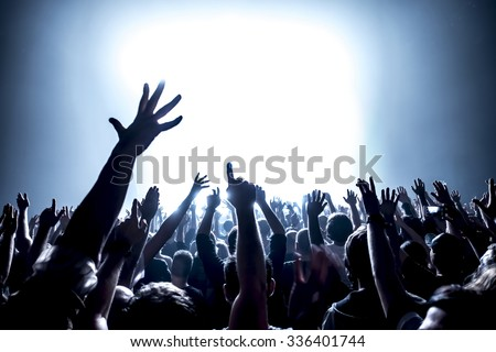 silhouettes of concert crowd in front of bright stage lights #336401744