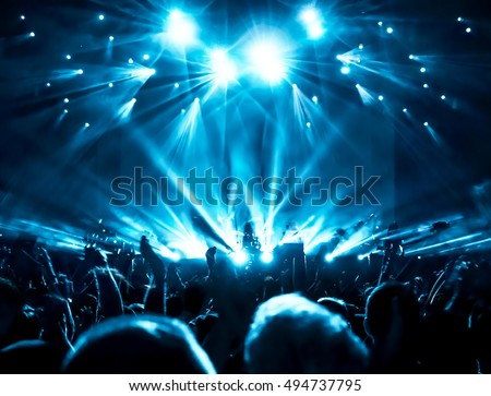 silhouettes of concert crowd in front of bright stage lights #494737795