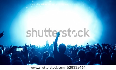 silhouettes of concert crowd in front of bright stage lights #528335464