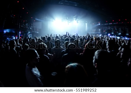 silhouettes of concert crowd in front of bright stage lights #551989252