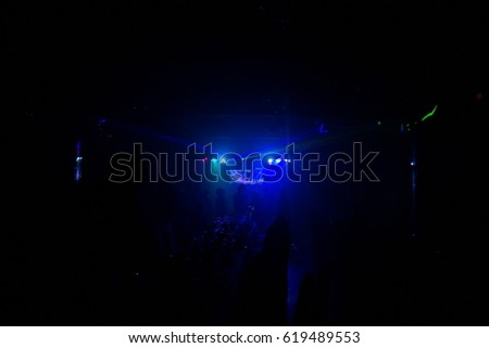 silhouettes of concert crowd in front of bright stage lights #619489553