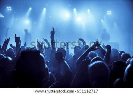 silhouettes of concert crowd in front of bright stage lights #651112717