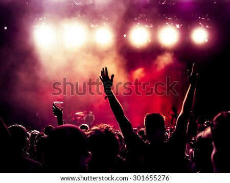 silhouettes of concert crowd in front of bright stage lights - a small DOF signifies that the focused area is narrow