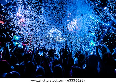 silhouettes of concert crowd in front of bright stage lights and confetti #633366287