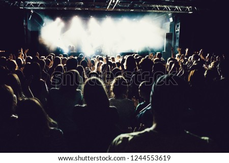 silhouettes of concert crowd in front of bright stage lights. cheering crowd of people with hands up on popular rock music concert. Dark background, smoke, concert spotlights. #1244553619