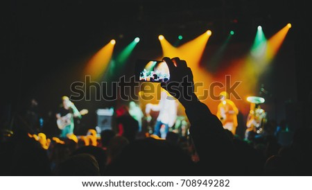silhouettes of concert crowd in front of bright stage lights. Dark background, smoke, concert  spotlights. Group of people holding hands with mobile phones at a concert  #708949282